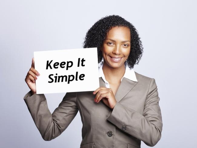 woman holding keep it simple board